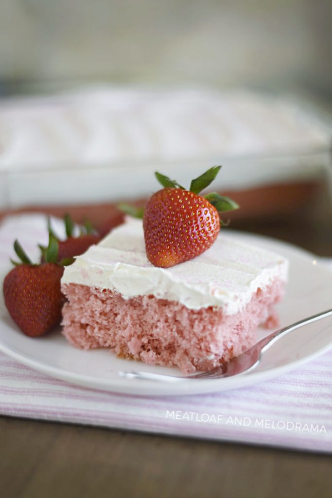 strawberry cream soda cake with cool whip topping and strawberry on plate