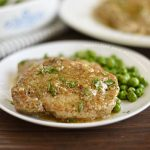 instant pot boneless pork chops on a plate with gravy and peas