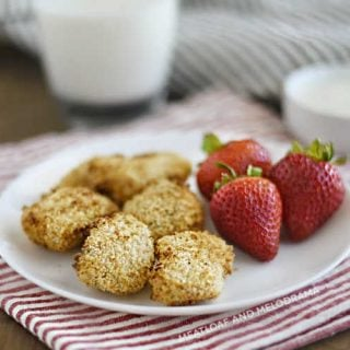 air fryer chicken nuggets with panko breadcrumbs and strawberries on a white plate