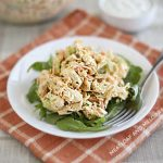 Instant Pot buffalo chicken salad over arugula on a white plate