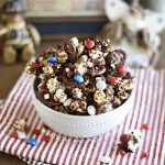patriotic pretzel popcorn snack mix with red white and blue candies in white bowl