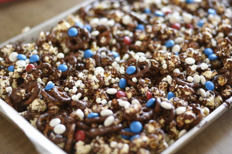 red white and blue snack mix with pretzels and popcorn and chocolate drizzle on tray