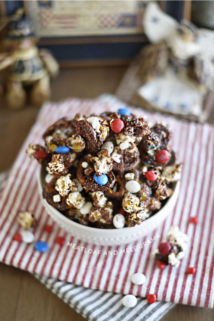 bowl of patriotic snack mix made with pretzels and popcorn with dark chocolate and red white and blue candies