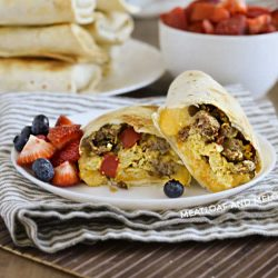 breakfast burritos made in the air fryer on a plate with strawberries and blueberries