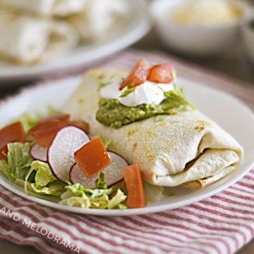 air fryer chicken chimichanga with sour cream and guacamole on a white plate