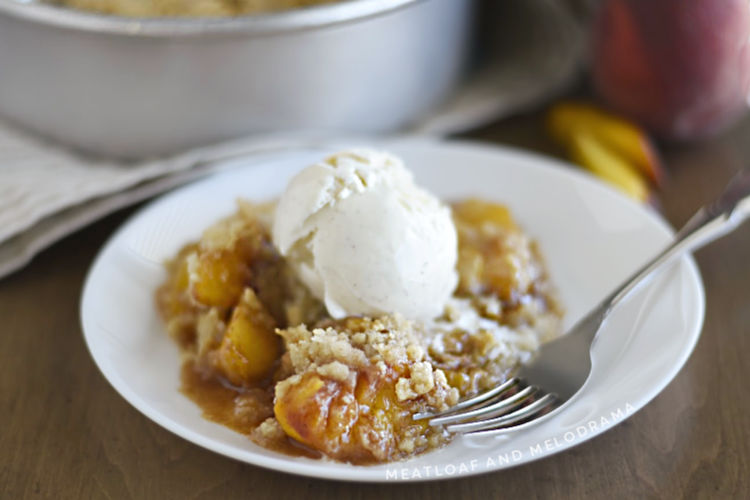 air fryer peach crisp topped with vanilla ice cream on a white plate