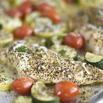 baked chicken with zucchini, yellow squash and grape tomatoes on a sheet pan