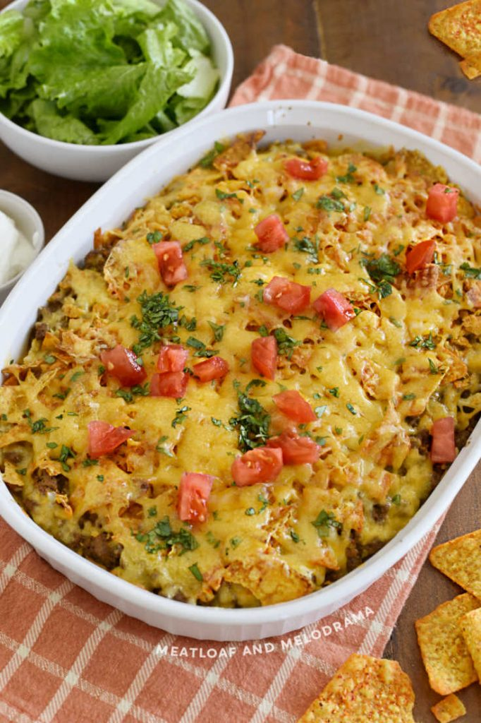 dorito taco bake topped with tomatoes and cilantro in white baking dish