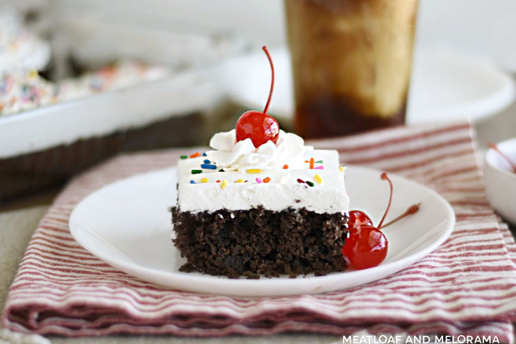 slice of chocolate root beer float cake with cool whip frosting and a cherry on top