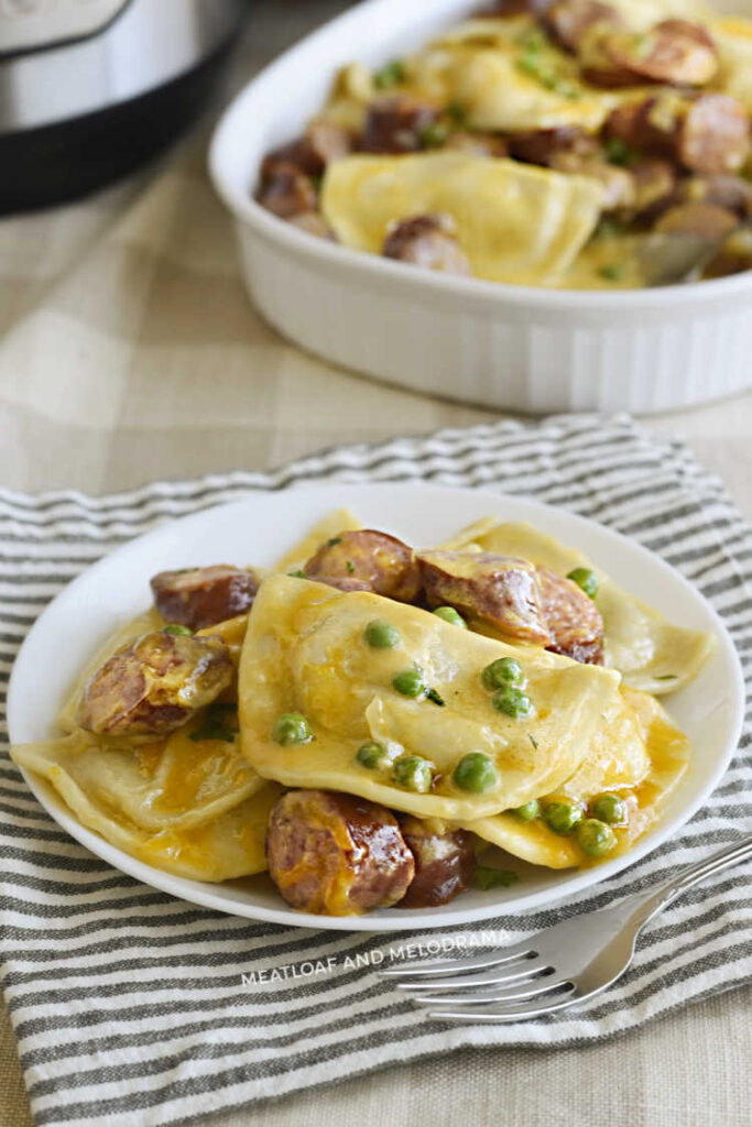 plate of pierogi and kielbasa and peas in cheddar cheese sauce on a white plate with casserole dish in background