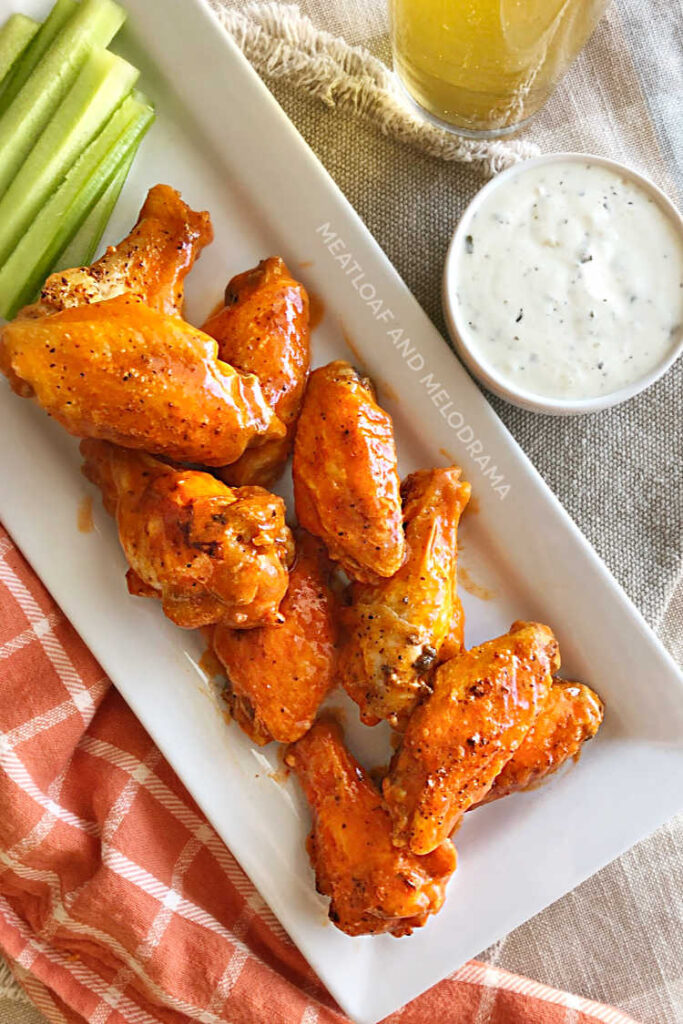 air fryer buffalo wings on white serving tray with celery and ranch dressing