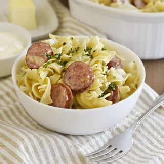 instant pot cabbage and noodles and kielbasa in white bowl