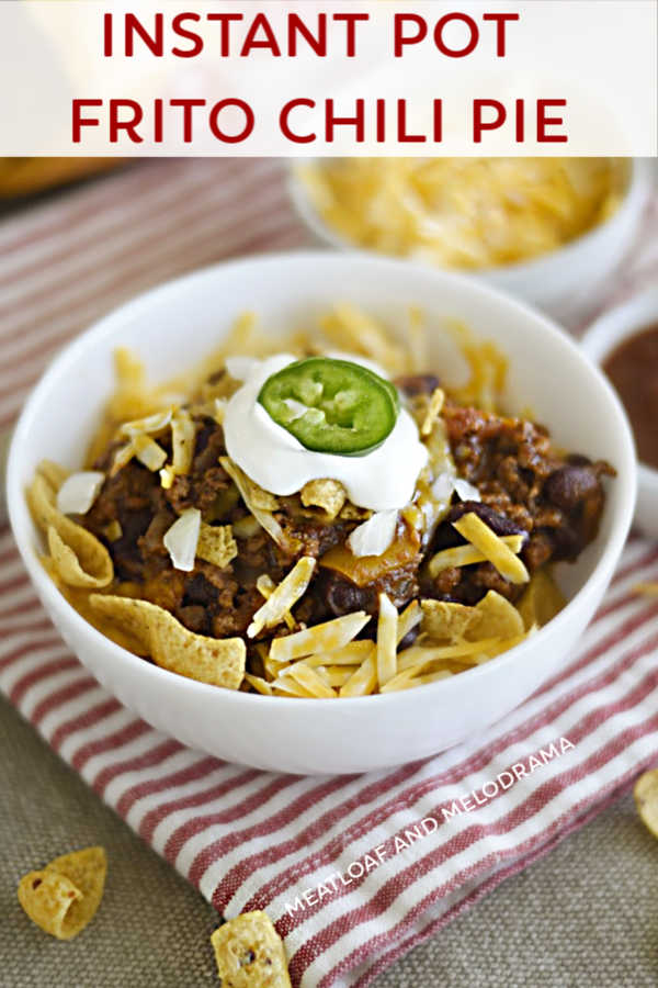 instant pot frito chili pie with corn chips, cheese and sour cream in a bowl