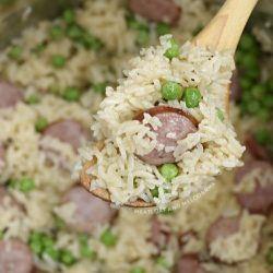 kielbasa with rice and peas on wooden spoon in the pressure cooker