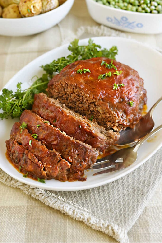 glazed meatloaf topped with parsley on a white platter
