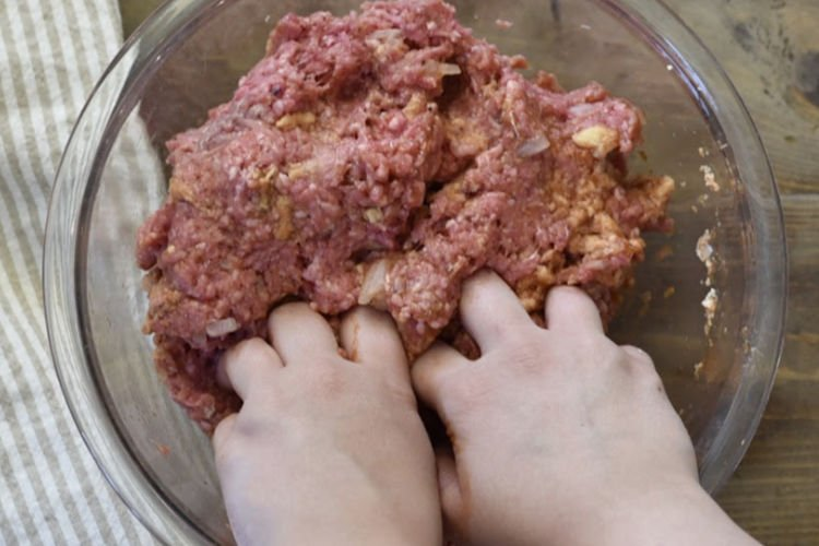 mixing meatloaf ingredients in a glass bowl