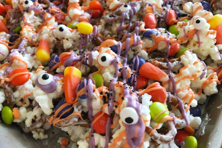 candy corn and candy eyes with melted chocolate over popcorn and pretzels