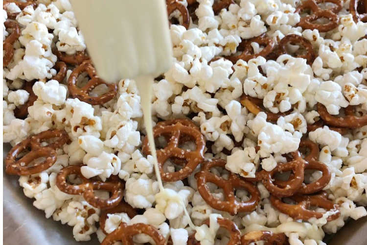 pour white chocolate over popcorn and pretzels for halloween treat