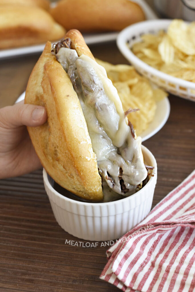 dip french dip sandwich made with beef chuck roast and melted provolone cheese in au jus gravy in white ramekin