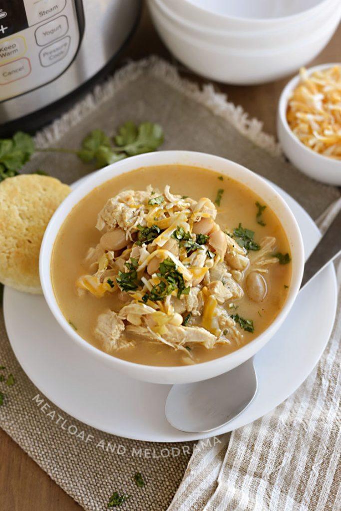 Instant Pot white chicken chili with white beans, corn and cheese in a white bowl with cilantro