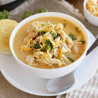 bowl of instant pot white chicken chili with white beans, corn and cheese and cilantro