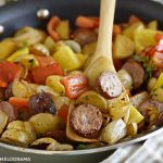 fried kielbasa with potatoes, peppers and onions on wooden spoon in a skillet