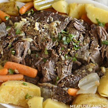 oven baked chuck roast with baby carrots, potatoes, celery and onions on a white platter