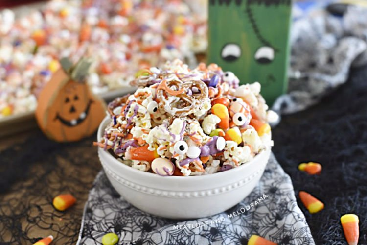 monster munch halloween snack mix made with popcorn, pretzels and candy in a white bowl with halloween decorations