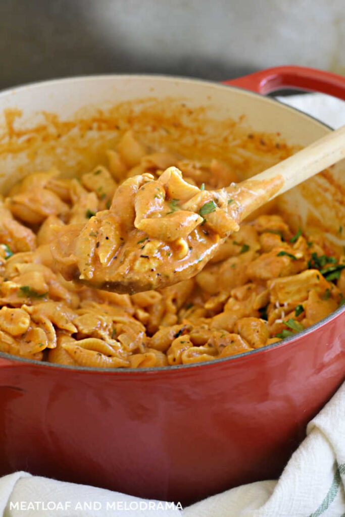 shell pasta and chicken in a creamy tomato sauce on a wooden spoon