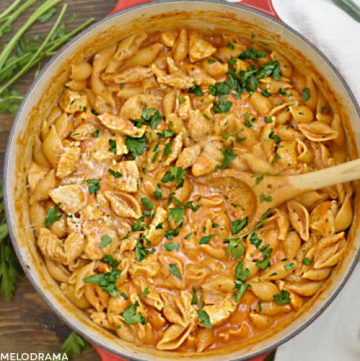 chicken and pasta shells in a creamy tomato sauce cooked in red dutch oven with wooden spoon and topped with parsley