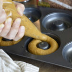 pipe cake mix into donut pan with piping bag