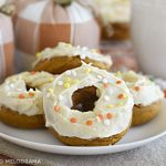pumpkin spice cake mix donuts with cream cheese frosting and fall sprinkles on a white plate with cloth pumpkins