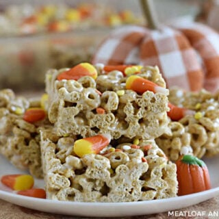 pumpkin spice cheerios treats with candy corn on a white plate with pumpkins