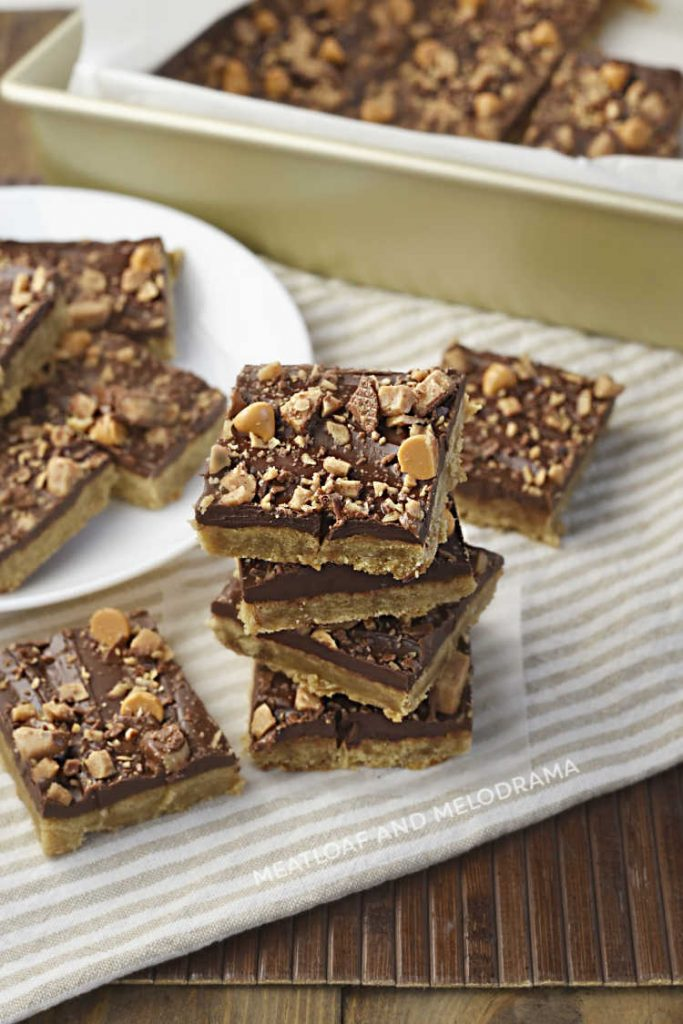toffee bar cookies with chocolate and butterscotch chips stacked up on a napkin