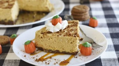 instant pot pumpkin cheesecake with gingerbread crust on a white plate with whipped cream, caramel and marshmallow pumpkins
