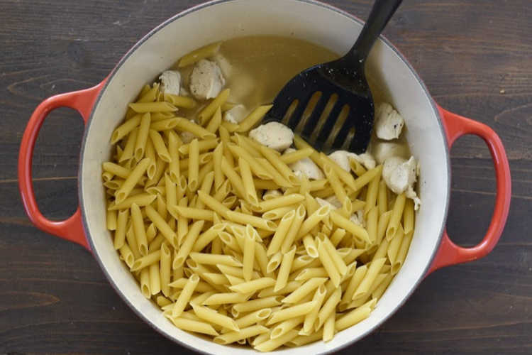 diced chicken breasts and uncooked penne pasta in large pot