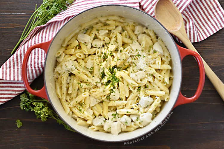 one pot chicken alfredo with penne pasta in a red dutch oven with parsley