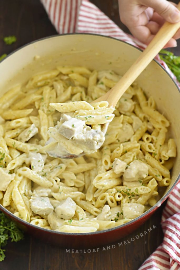 chicken alfredo penne pasta on a wooden spoon in dutch oven