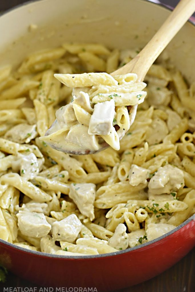 creamy chicken alfredo and penne pasta on a spoon in large pot