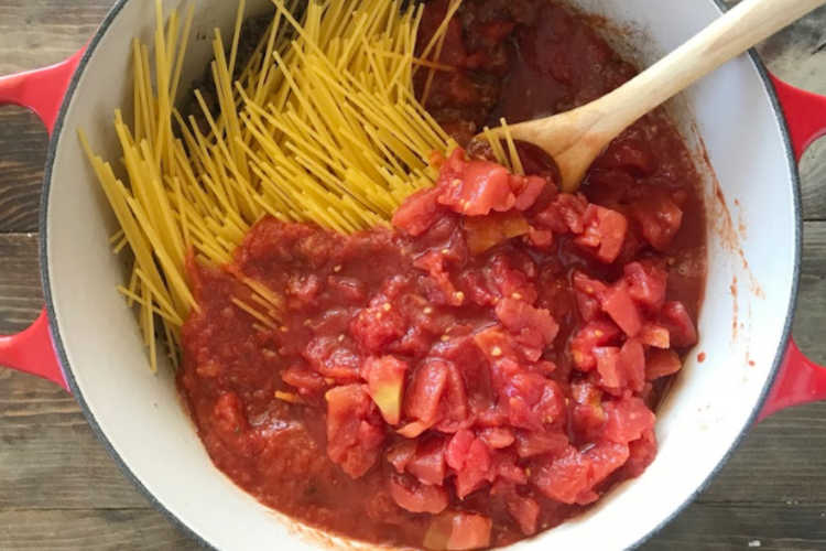 uncooked spaghetti noodles with diced tomatoes, pasta sauce and meat in red dutch oven