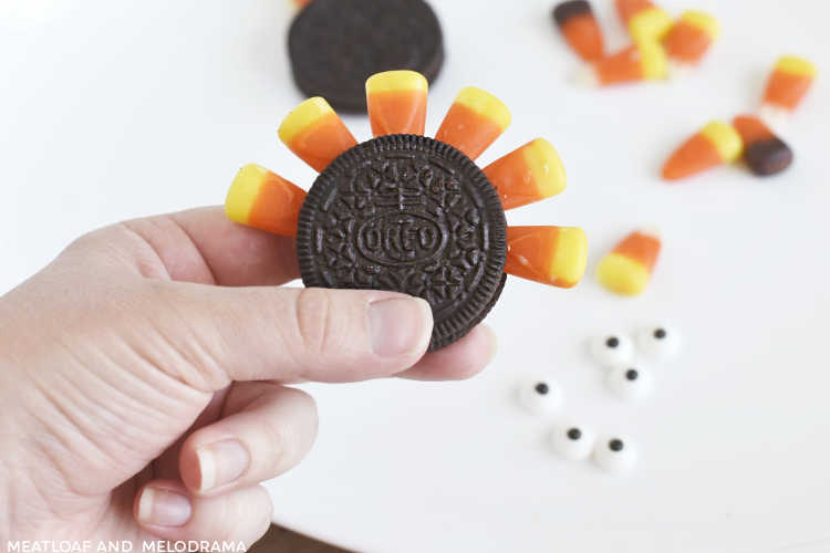 hand holding oreo cookie with candy corn in middle