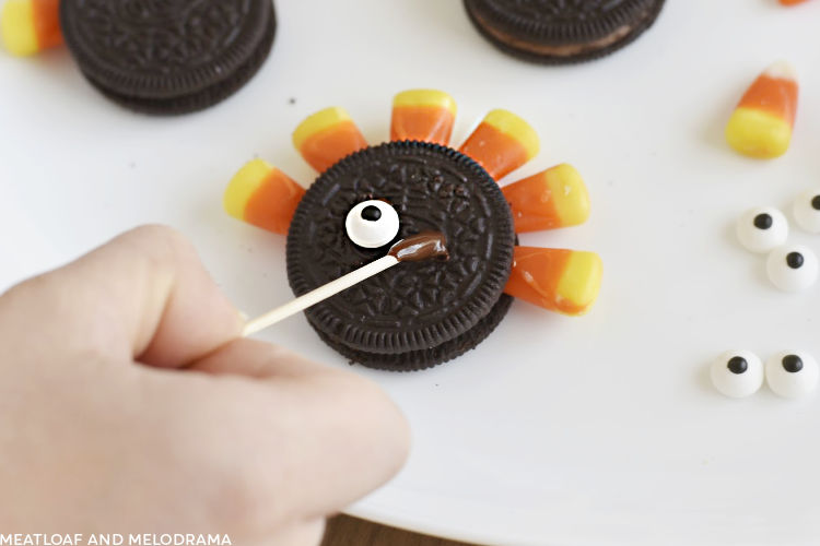 apply melted chocolate to oreo with toothpick