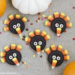 turkey cookies made with oreos, candy corn and candy eyes on a brown placemat with pumpkins