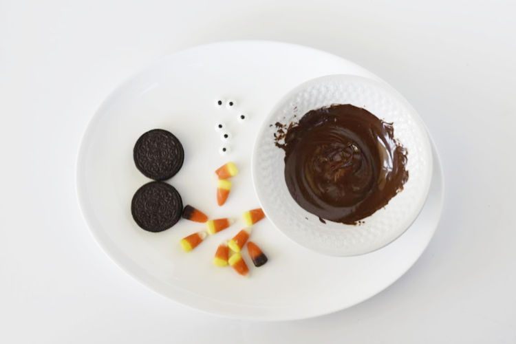 oreo cookies, candy corn, candy eyes and melted chocolate on a tray