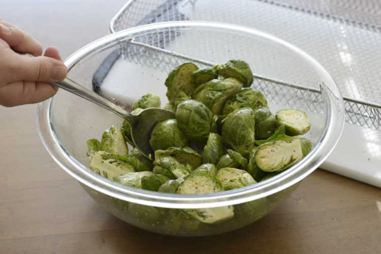 toss cut brussels sprouts with olive oil, salt and pepper in a bowl