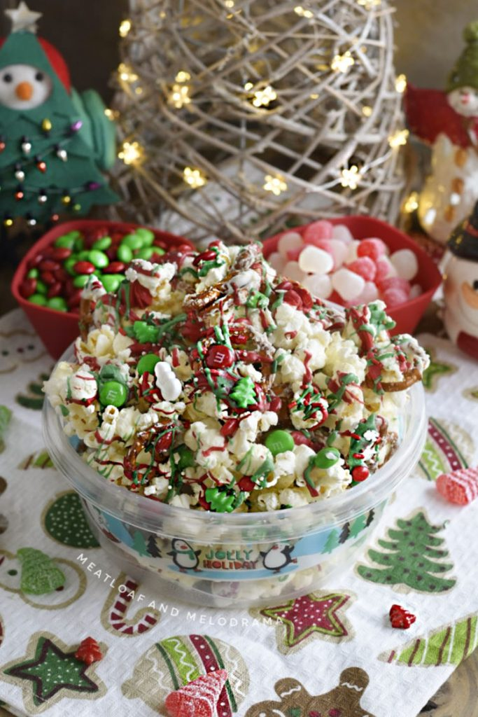 bowl of christmas crunch popcorn pretzel snack mix with holiday candies on table