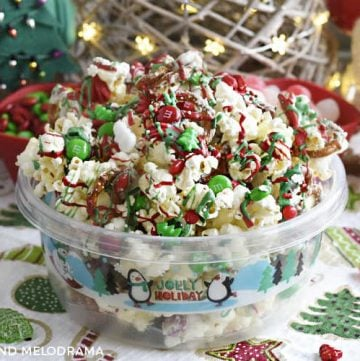 christmas crunch snack mix made with popcorn pretzels and candy in a holiday container
