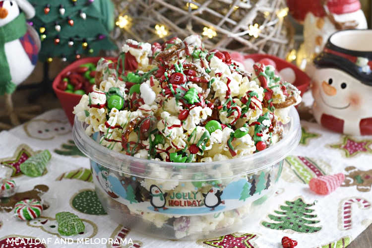 christmas crunch snack mix with popcorn, pretzels and candy in a holiday container