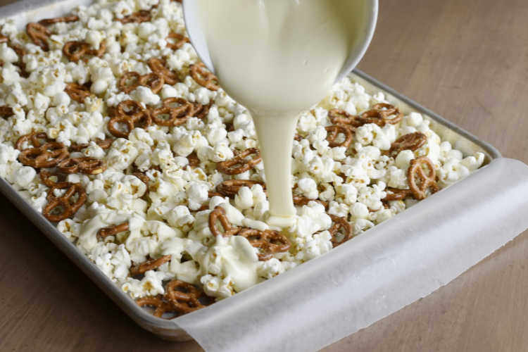 pour melted white chocolate over pretzels and popcorn