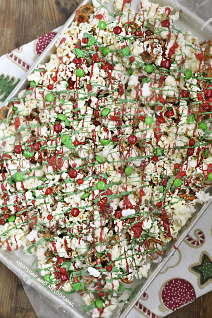 christmas crunch snack mix with pretzels, popcorn and red and green candy on a baking tray